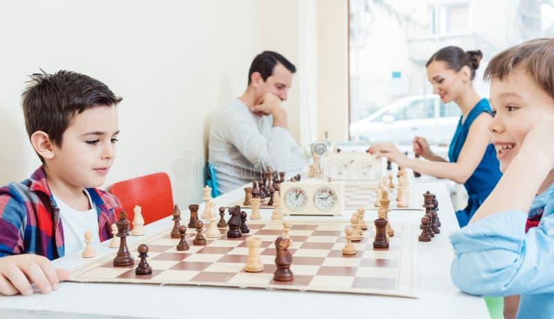 Familj som spelar schack i turneringrum arkivfoton