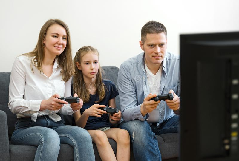 Familj som spelar videospelet arkivfoto
