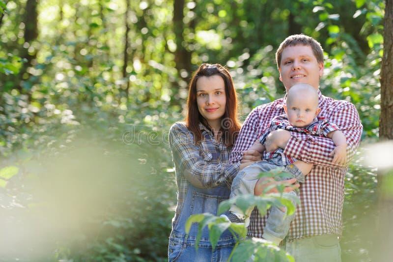 Familj som spenderar tid i skogen i sommaren royaltyfri bild