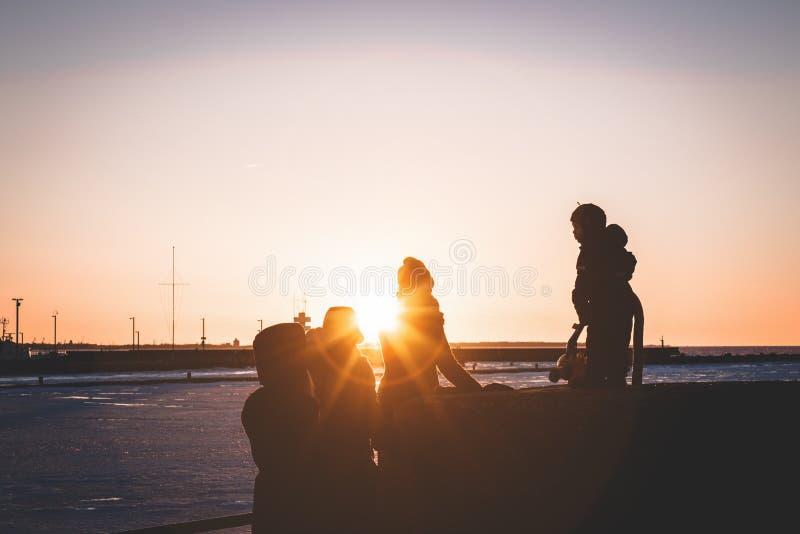 Familj som spenderar tid under solnedgången vid havet royaltyfria foton