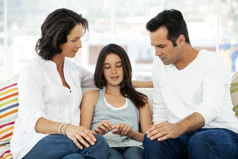 Familj som talar - föräldrar som hemma talar med dottern royaltyfri fotografi