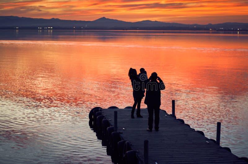 Familj som tar bilder i solnedgången av det lugna vattnet av Albuferaen de Valencia, Spanien royaltyfri fotografi
