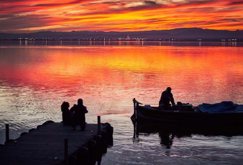 Familj som tar bilder i solnedgången av det lugna vattnet av Albuferaen de Valencia, Spanien royaltyfria foton