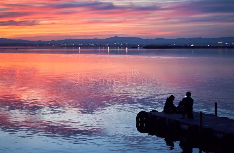 Familj som tar bilder i solnedgången av det lugna vattnet av Albuferaen de Valencia, Spanien royaltyfri foto