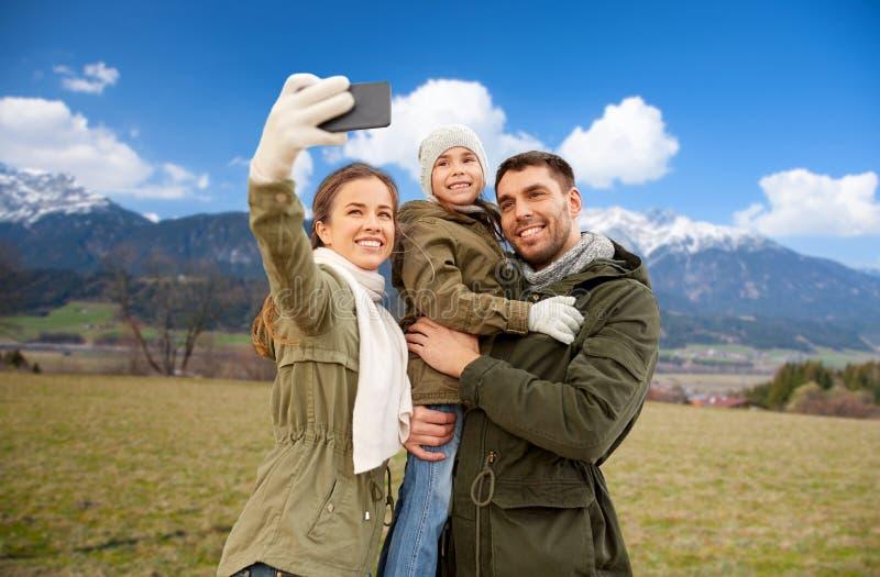 Familj som tar selfie vid smartphonen över fjällängar royaltyfri bild