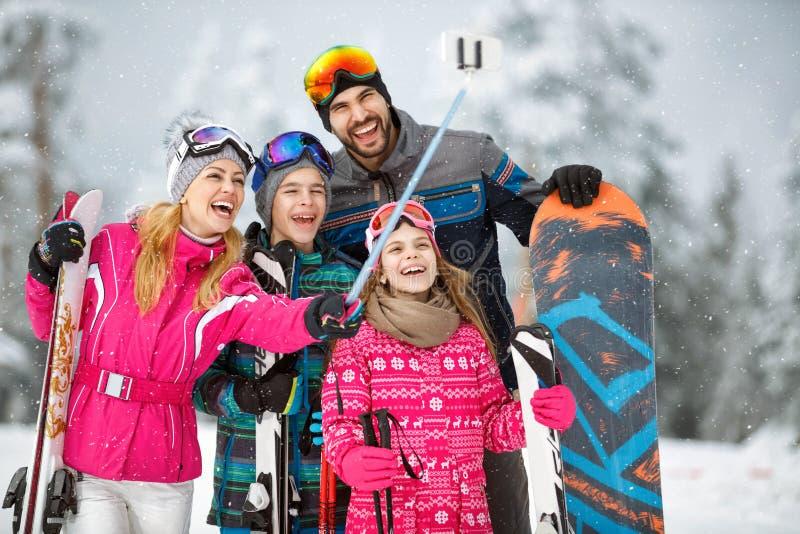 Familj som tar selfiefotoet, medan skida i snö arkivbild