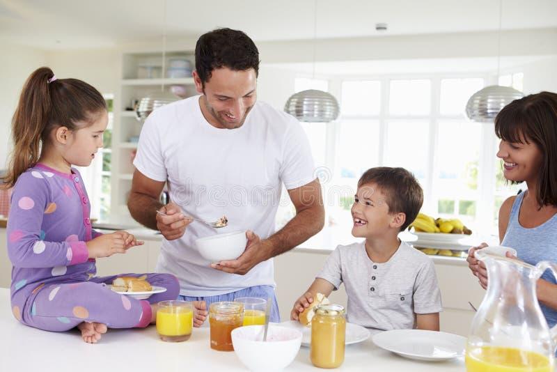 Familj som tillsammans äter frukosten i kök arkivbilder