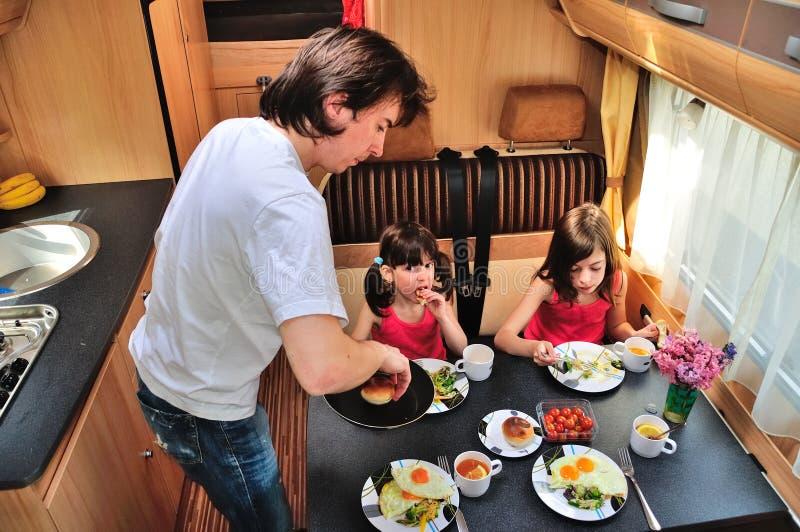 Familj som tillsammans äter i RV-inre, lopp i motorhomecamparen, husvagn på semester med ungar royaltyfri fotografi