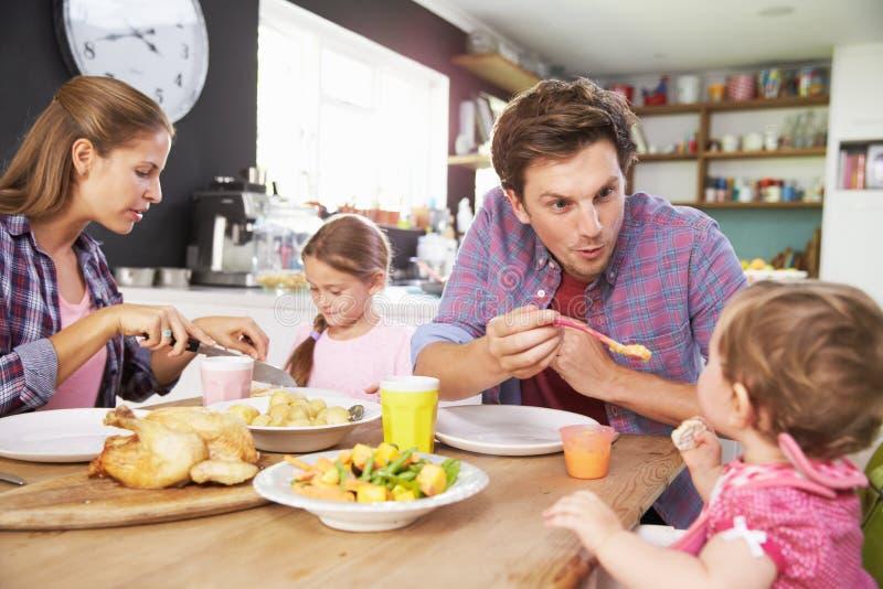 Familj som tillsammans äter mål i kök royaltyfria foton