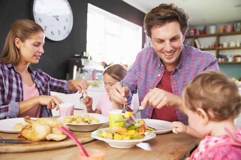 Familj som tillsammans äter mål i kök arkivfoto