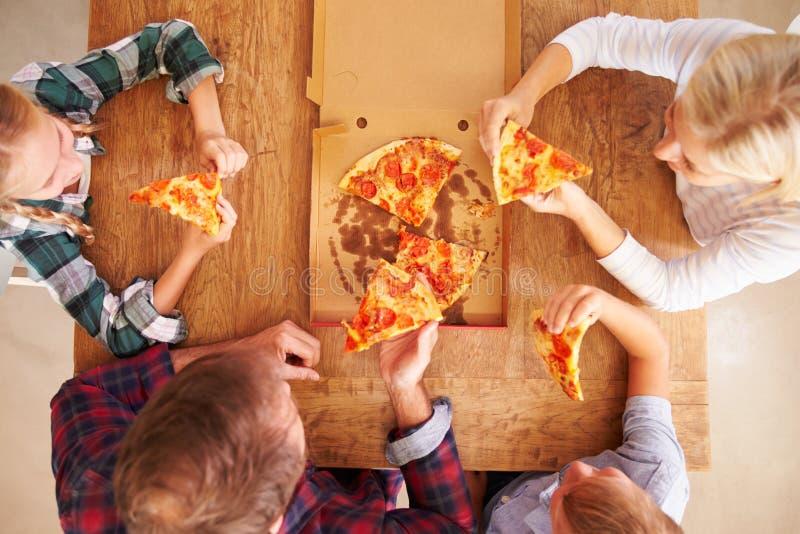 Familj som tillsammans äter pizza, över huvudet sikt arkivfoton