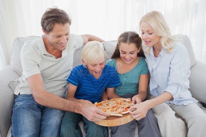 Familj som tillsammans äter pizza arkivbilder