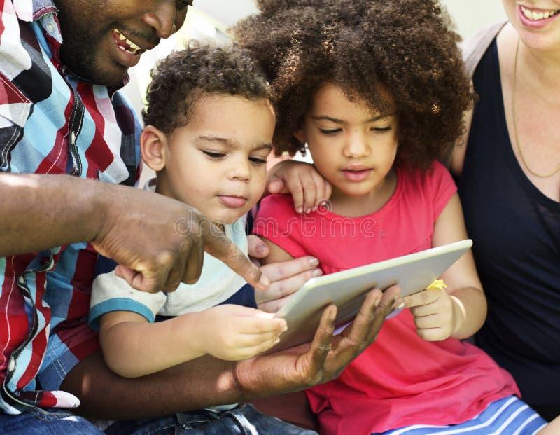 Familj som tillsammans använder en minnestavla royaltyfria foton