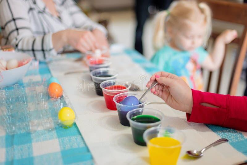 Familj som tillsammans färgar påskägg royaltyfria foton