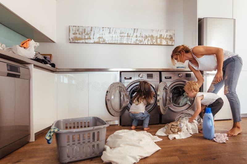Familj som tillsammans gör tvätterit hemma royaltyfria bilder