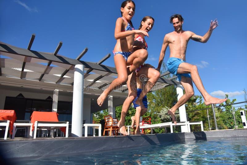 Familj som tillsammans hoppar till simbassängen royaltyfria foton
