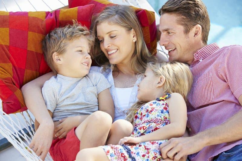 Familj som tillsammans kopplar av i trädgårds- hängmatta royaltyfria foton