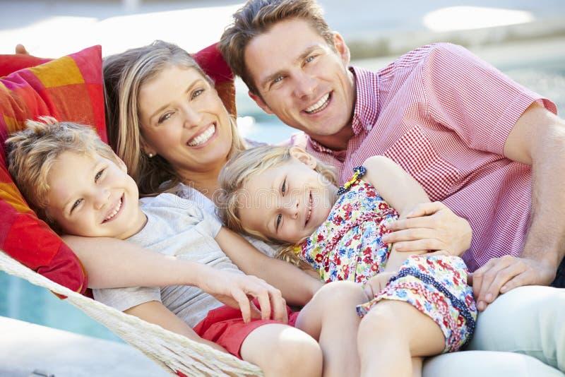 Familj som tillsammans kopplar av i trädgårds- hängmatta royaltyfria bilder