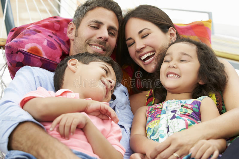 Familj som tillsammans kopplar av i trädgårds- hängmatta arkivfoto