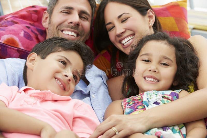 Familj som tillsammans kopplar av i trädgårds- hängmatta arkivbilder