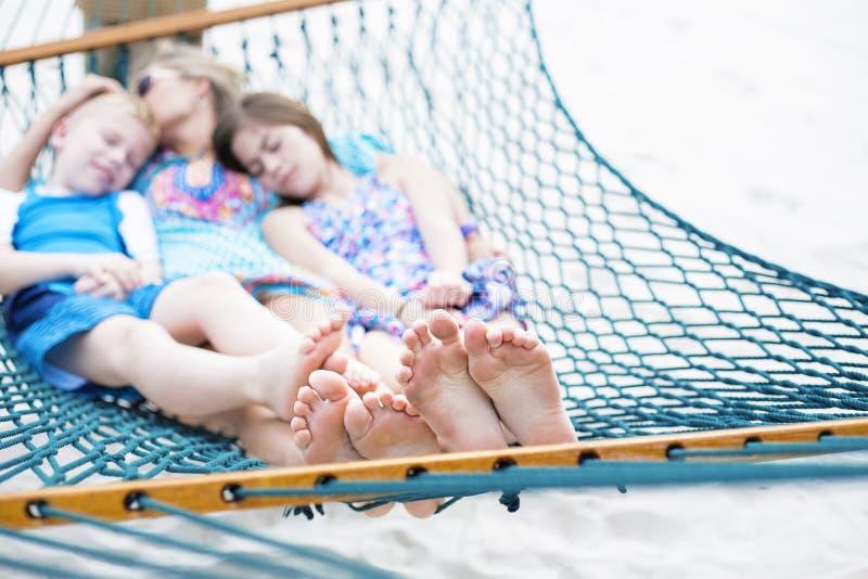 Familj som tillsammans kopplar av på en hängmatta, fokus på fot royaltyfri fotografi