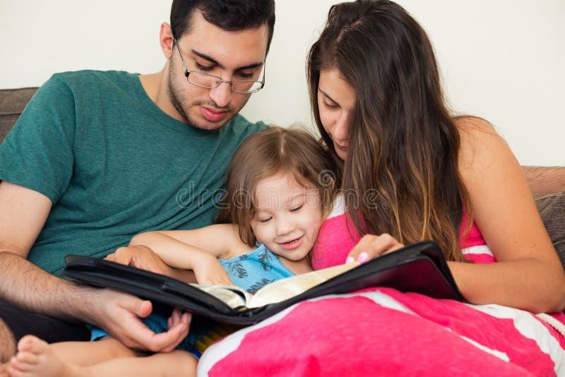 Familj som tillsammans läser bibeln arkivfoto