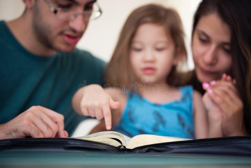 Familj som tillsammans läser bibeln royaltyfria bilder