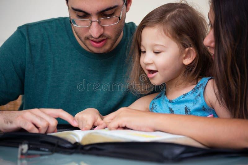 Familj som tillsammans läser bibeln arkivbild