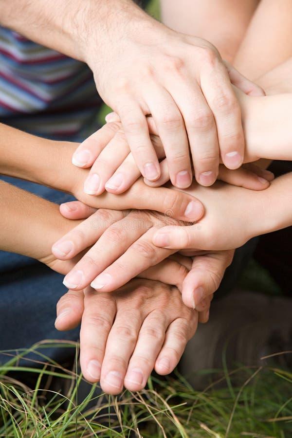 Familj som tillsammans sätter deras händer arkivfoton