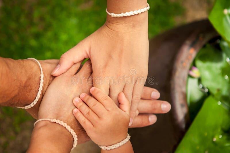 Familj som tillsammans sätter deras händer Begrepp för samhörighetskänsla och hjälp arkivfoton