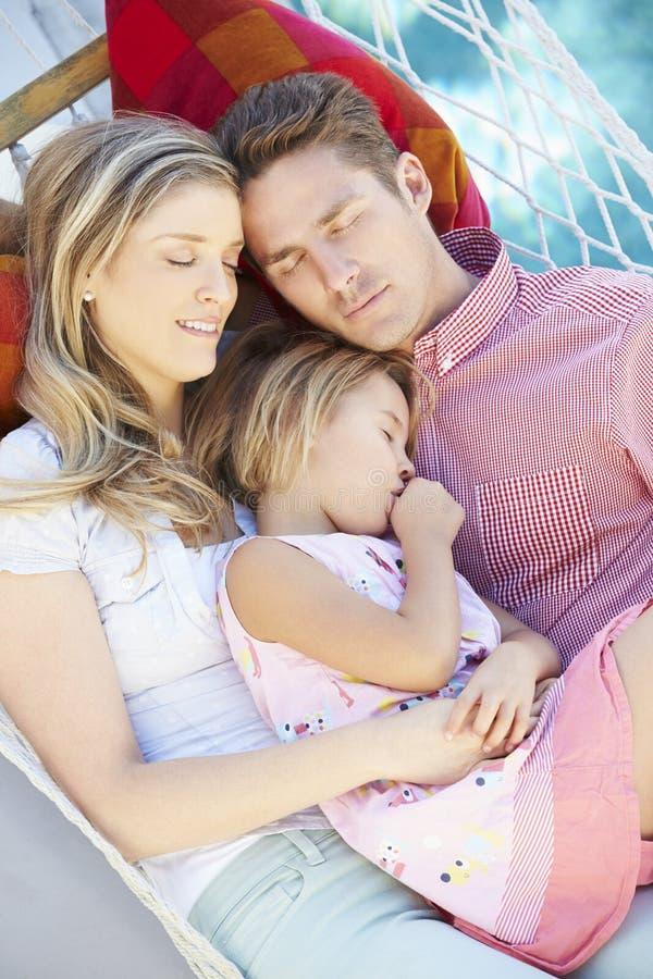 Familj som tillsammans sover i trädgårds- hängmatta royaltyfri bild