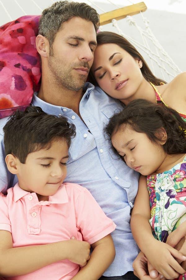 Familj som tillsammans sover i trädgårds- hängmatta fotografering för bildbyråer