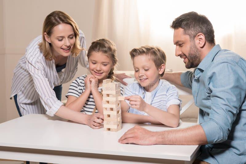 Familj som tillsammans spelar Jenga modigt hemmastatt arkivbilder