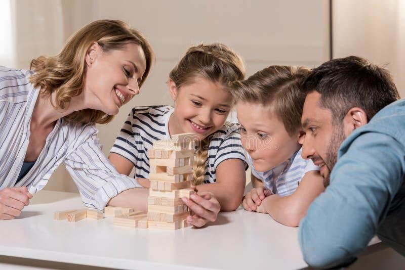 Familj som tillsammans spelar Jenga modigt hemmastatt arkivbild