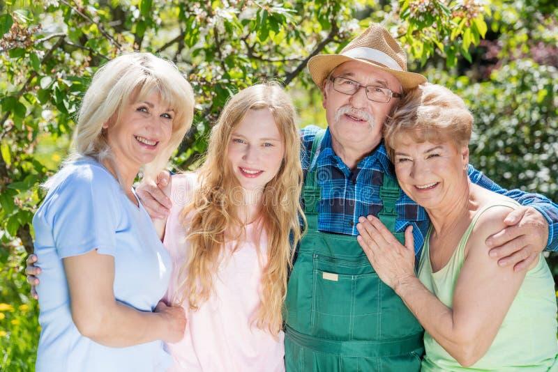 Familj som tillsammans spenderar tid i en sommarträdgård utvecklingar royaltyfria bilder