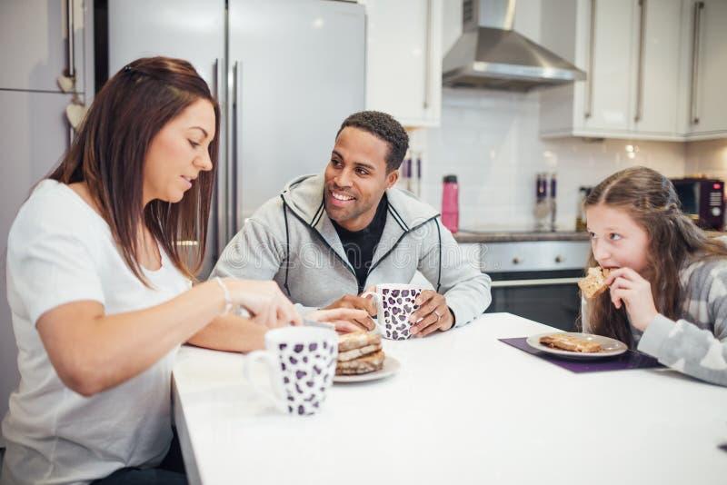 Familj som tillsammans tycker om frukosten arkivbilder