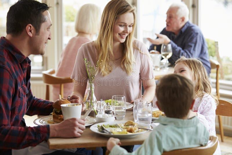 Familj som tillsammans tycker om mål i restaurang arkivbilder