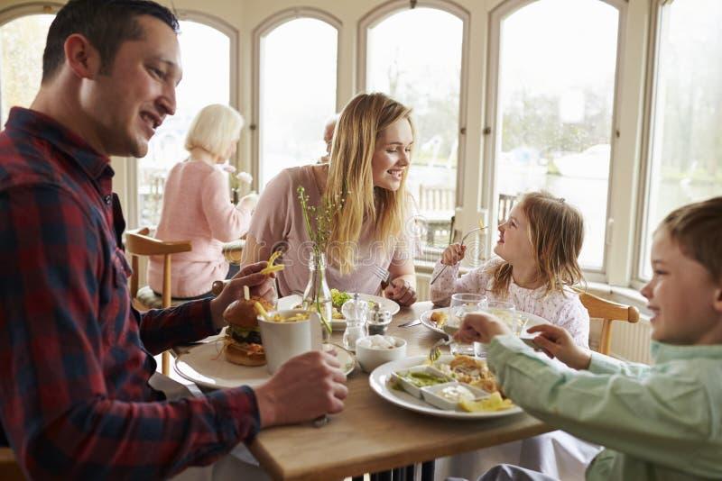 Familj som tillsammans tycker om mål i restaurang royaltyfria bilder