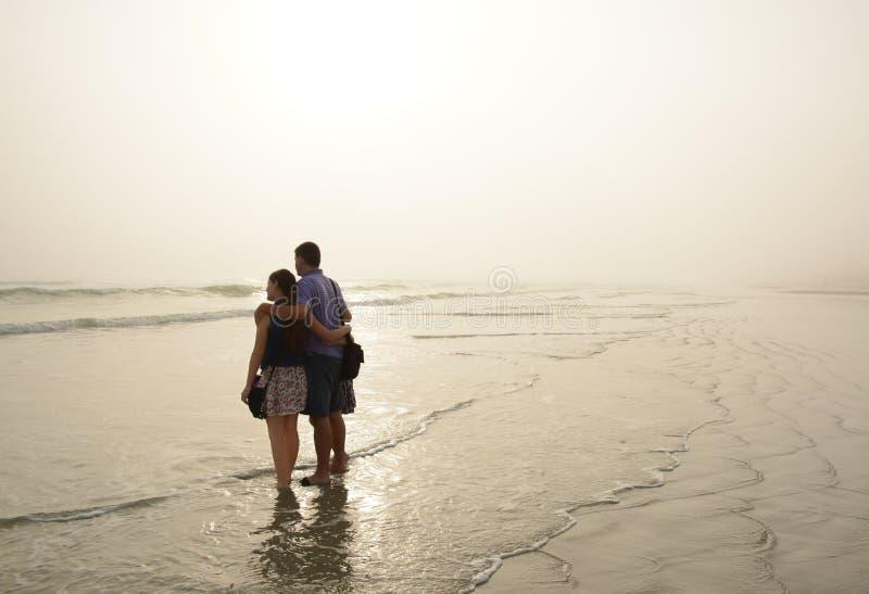 Familj som tillsammans tycker om tid på den härliga dimmiga stranden arkivbilder