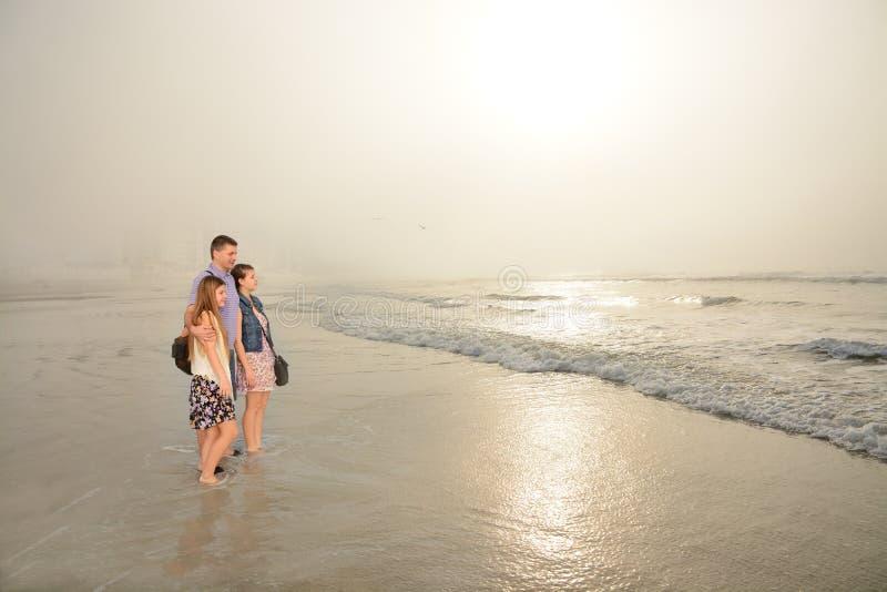 Familj som tillsammans tycker om tid på den härliga dimmiga stranden royaltyfri foto