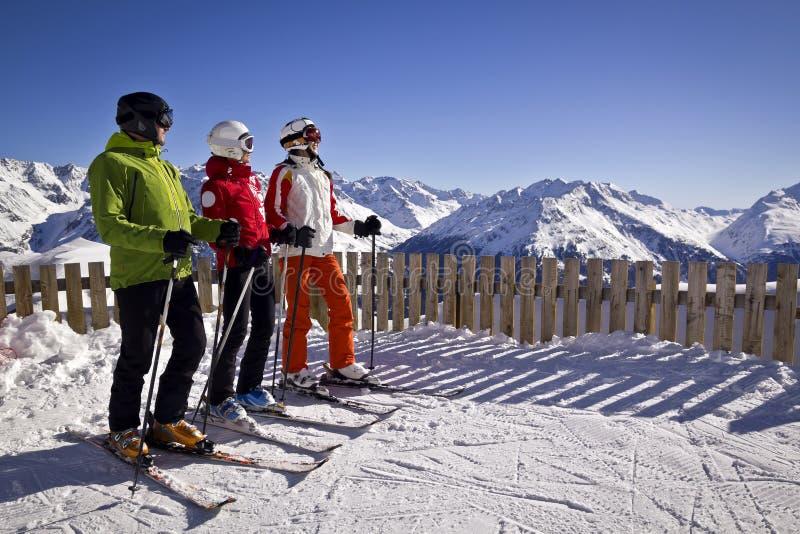 Familj som tycker om att skida i fjällängar royaltyfria bilder