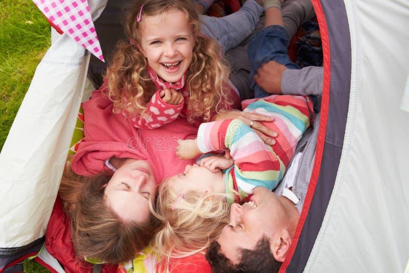 Familj som tycker om campa ferie på campingplats royaltyfri fotografi