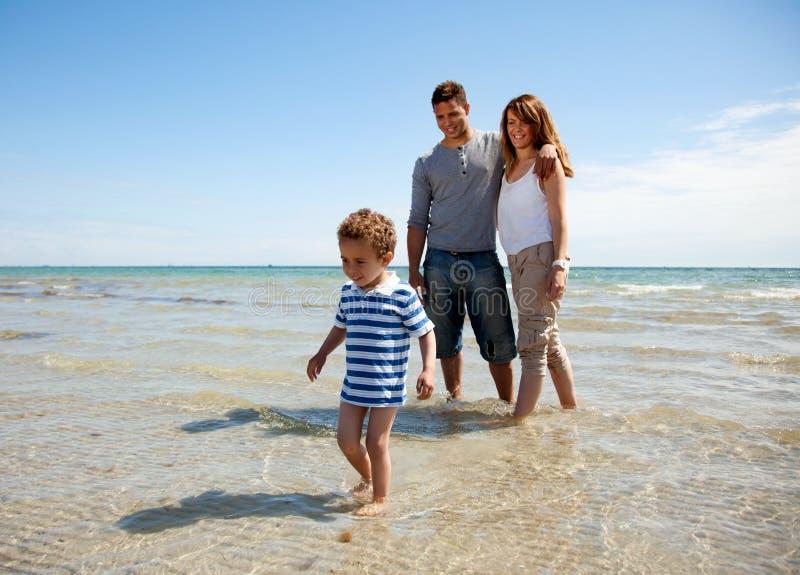 Familj som tycker om helgen på en solig strand royaltyfri foto