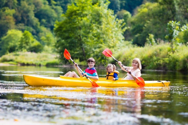 Familj som tycker om kajakritt på en flod royaltyfri bild