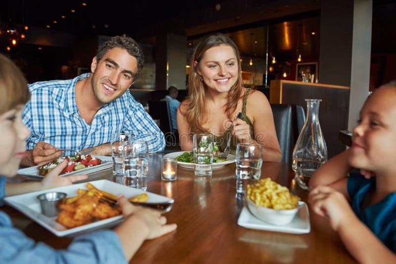 Familj som tycker om mål i restaurang royaltyfri foto