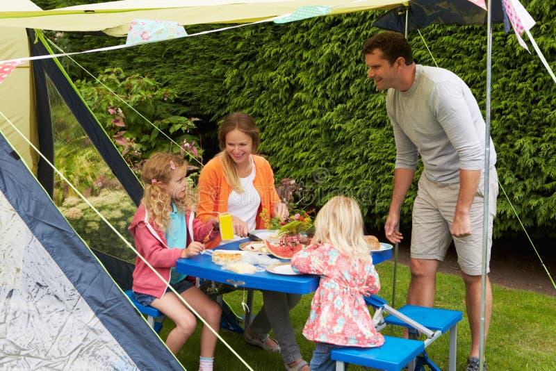 Familj som tycker om mål utanför tältet på campa ferie royaltyfri fotografi