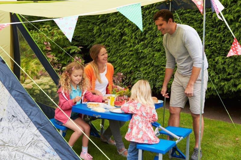 Familj som tycker om mål utanför tältet på campa ferie royaltyfri foto