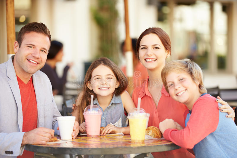 Familj som tycker om mellanmålet i CafÅ ½ royaltyfria foton