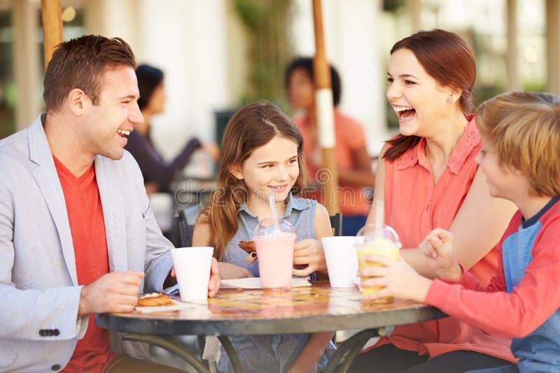 Familj som tycker om mellanmålet i CafÅ ½ royaltyfri foto