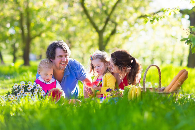 Familj som tycker om picknicken i blommande trädgård arkivbild